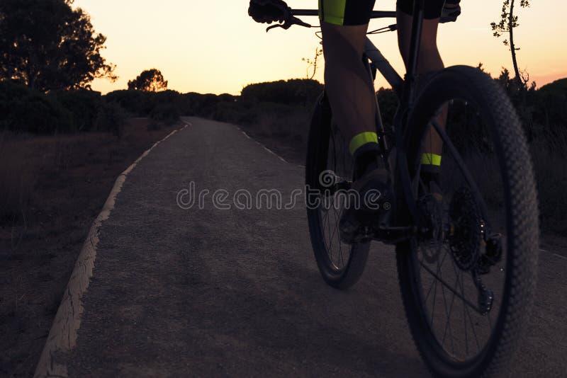 Велосипедист на горном велосипеде ехать путем на заходе солнца стоковое изображение