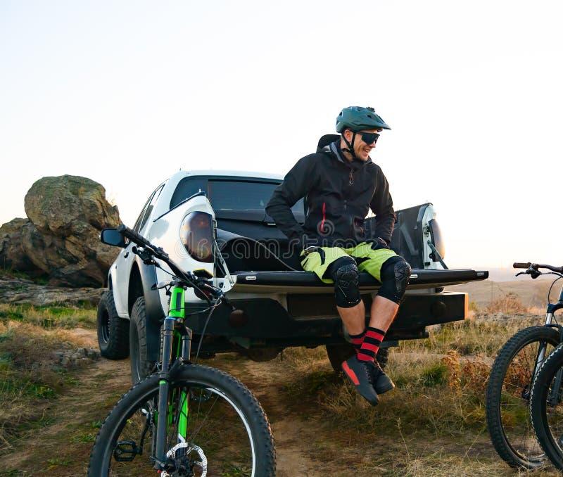 Велосипедист на приемистости с тележки дороги отдыхая после велосипеда ехать в горах и разговаривая с друзьями стоковые фото