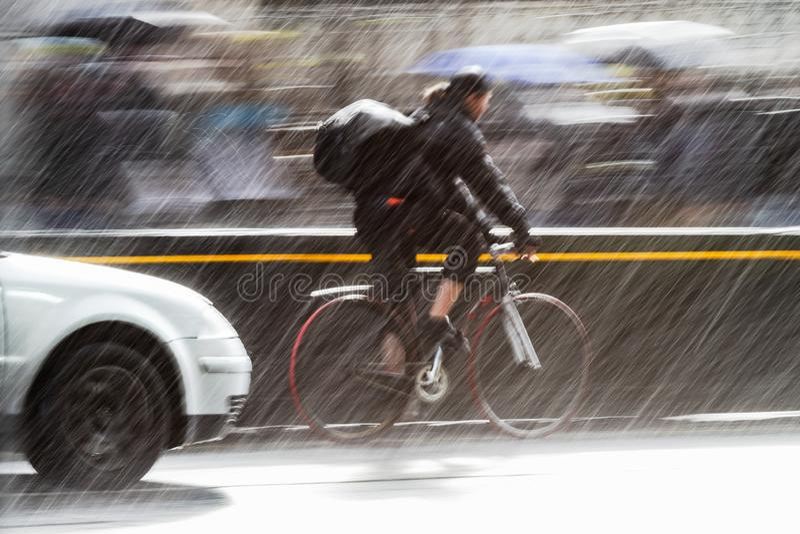 Велосипедист на улице города на проливном дожде стоковая фотография rf