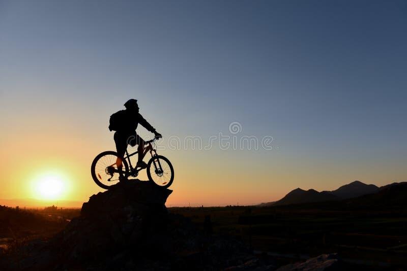 Велосипедист на утесе против солнца стоковое фото