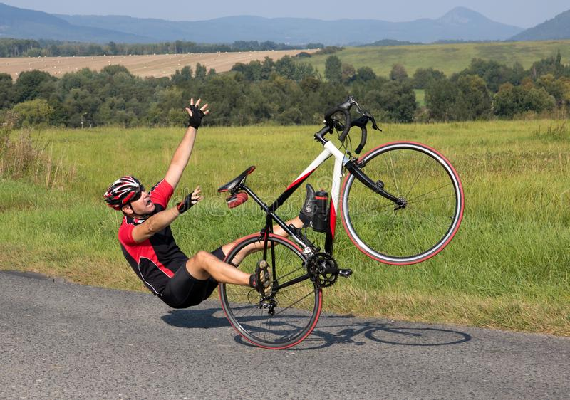 Велосипедист падает с велосипеда на дороге асфальта стоковая фотография