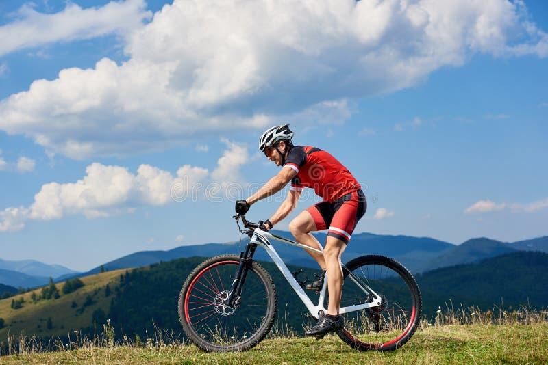 Велосипедист спортсмена спортсмена в профессиональном велосипеде sportswear и по пересеченной местностей шлема ехать стоковые фотографии rf