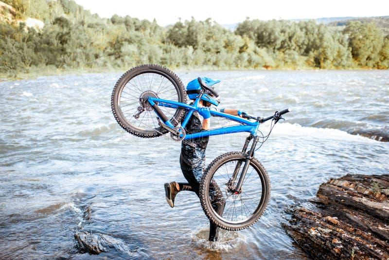 Велосипедист с велосипедом на горах стоковые фотографии rf