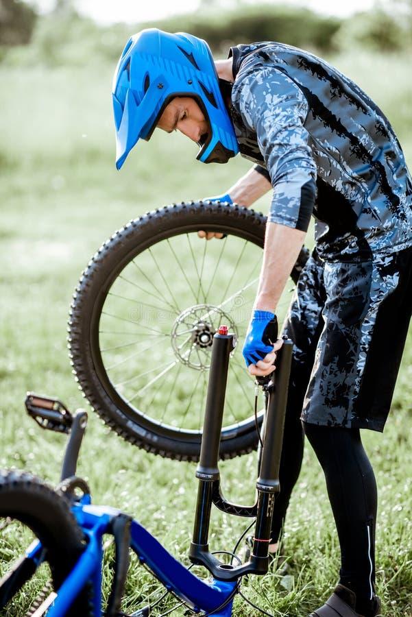 Велосипедист reparing его велосипед outdoors стоковые фотографии rf