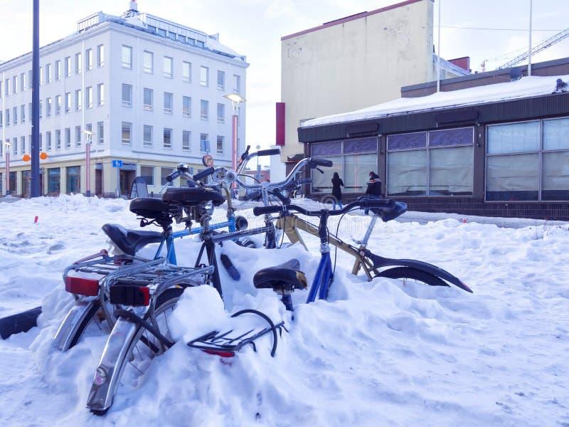 Велосипеды города покрытые на снеге в улице стоковое фото rf