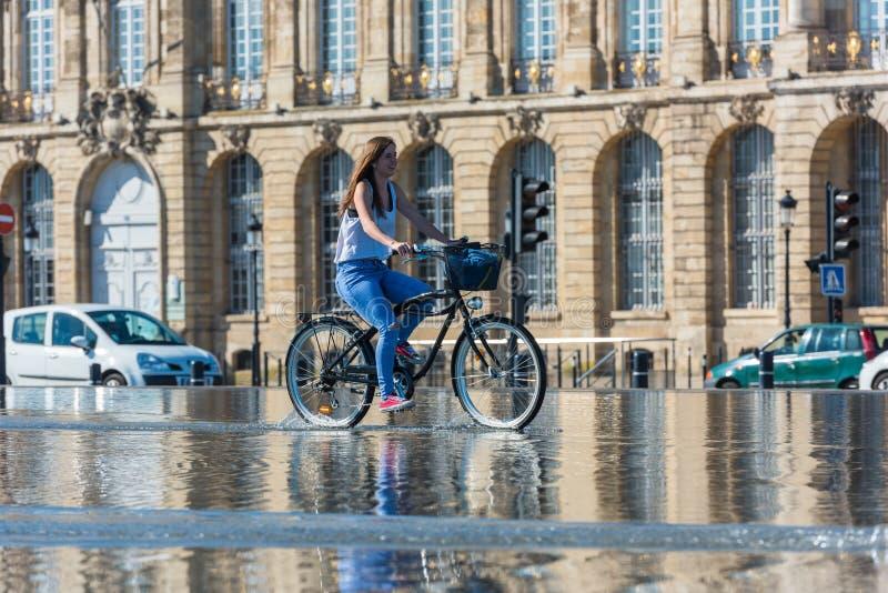 Велосипеды людей ехать в фонтане в Бордо, Франции стоковые фотографии rf