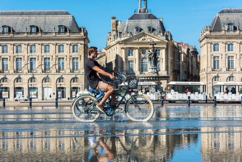 Велосипеды людей ехать в фонтане в Бордо, Франции стоковая фотография