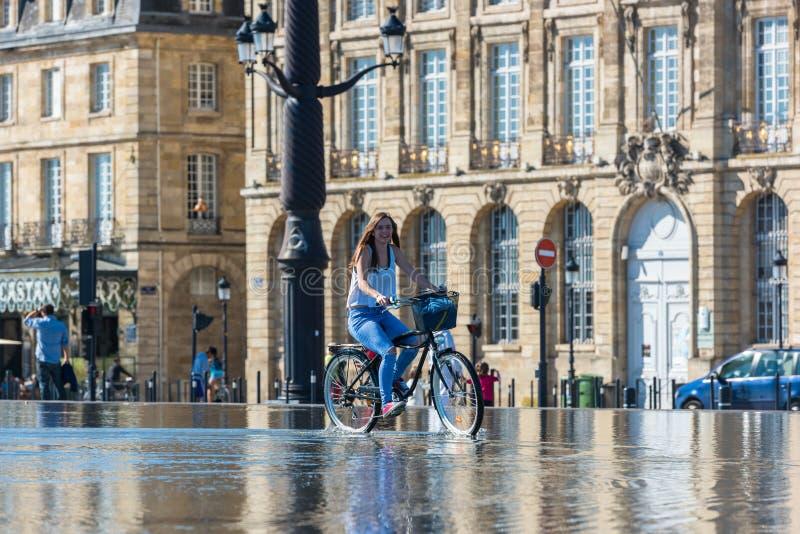 Велосипеды людей ехать в фонтане в Бордо, Франции стоковое изображение rf