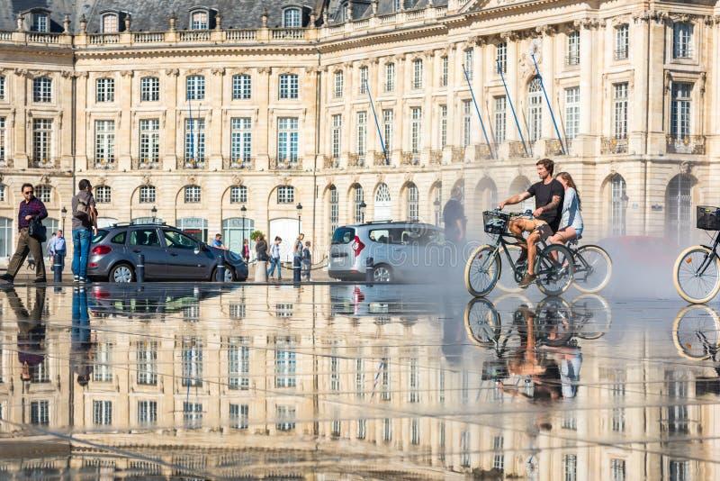 Велосипеды людей ехать в фонтане в Бордо, Франции стоковые изображения rf