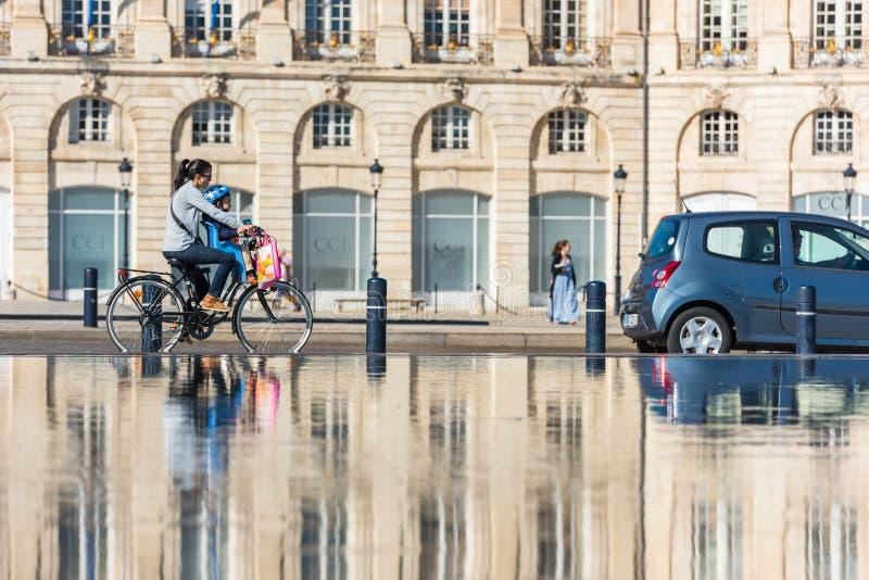 Велосипеды людей ехать в фонтане в Бордо, Франции стоковые изображения