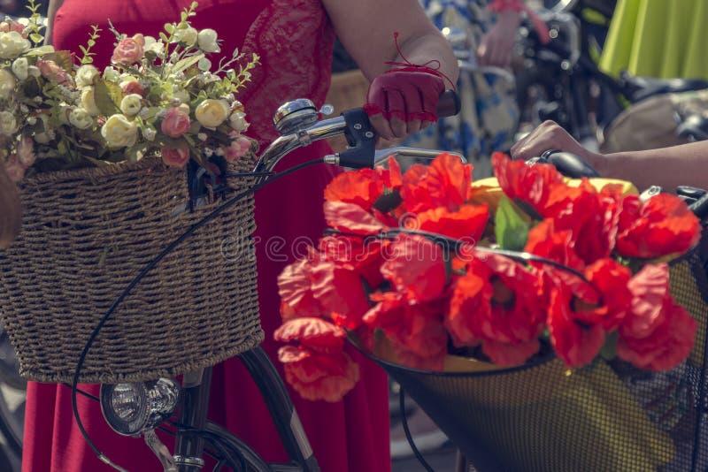 Велосипеды с корзинами цветков Женщина в красной юбке держит handlebar стоковые фотографии rf