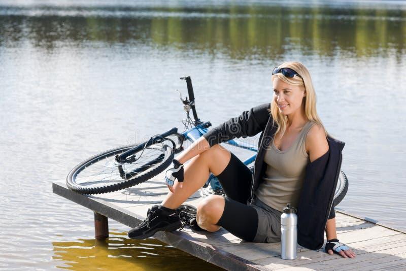 велосипед детеныши женщины спорта озера сидя стоковая фотография