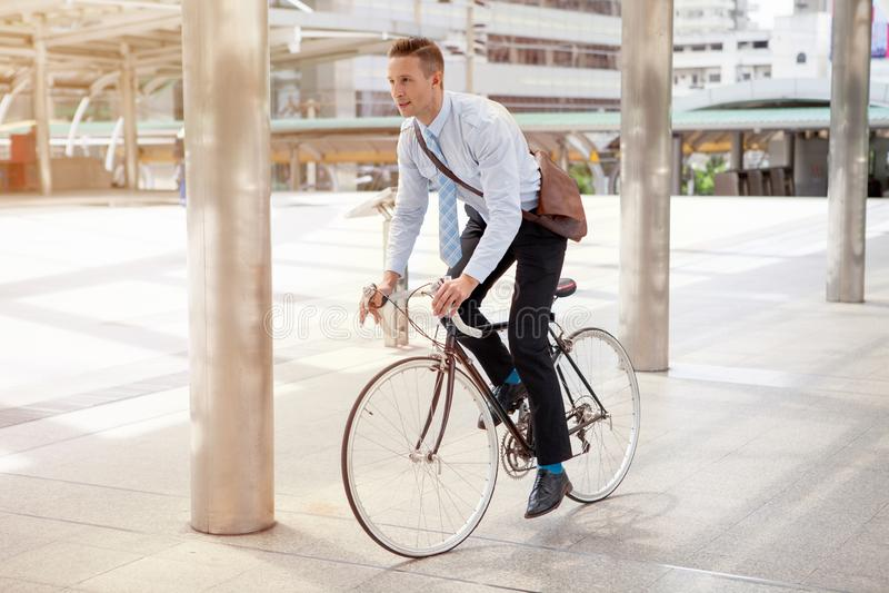 Велосипед катания бизнесмена, который нужно работать на городской улице в утре переход и здоровое стоковые фотографии rf
