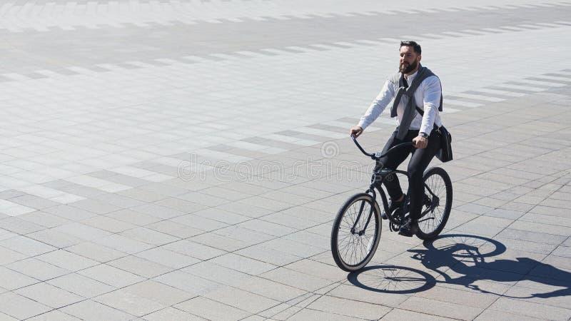 Велосипед катания бизнесмена к рабочему месту для защищая окружающей среды стоковая фотография