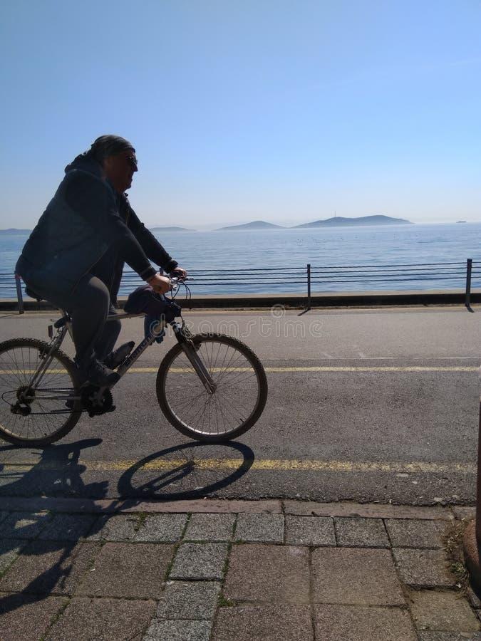 Велосипед катания человека около моря стоковые фотографии rf