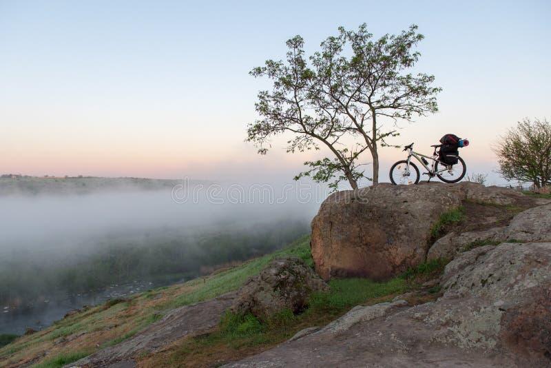 Велосипед над туманным каньоном, рекой и камнями стоковая фотография