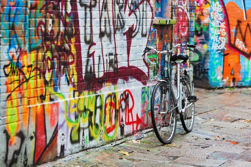 Велосипед стоит на стене надписи на стенах стоковая фотография rf