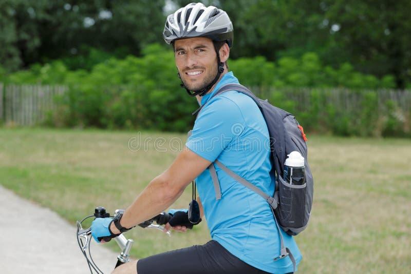 Велосипед человека в траве naturedeep стоковое изображение