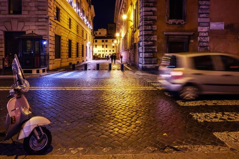 Велосипед Vespa и автомобили проходить в центральном Риме город освещает место ночи стоковое фото rf