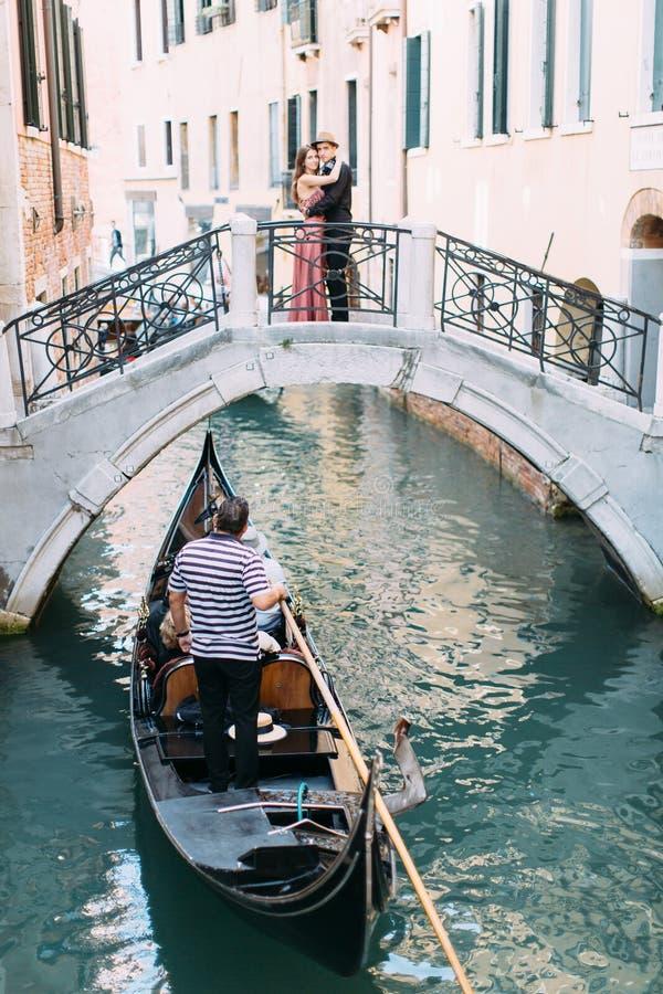 Венецианский пейзаж с гондолой на узком канале Романтичное положение пар на мосте венецианского канала стоковое фото