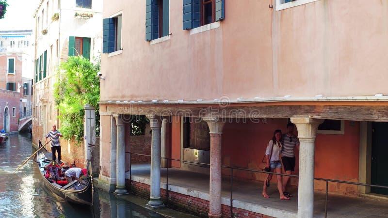 ВЕНЕЦИЯ, ИТАЛИЯ - 8-ОЕ АВГУСТА 2017 Молодые пары идя вдоль венецианского канала с известной гондолой стоковое изображение rf