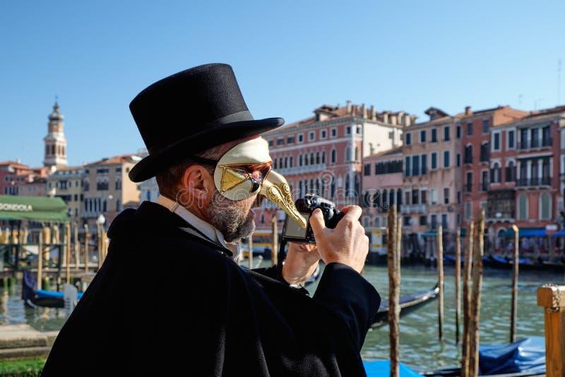 Венеция, Италия - 10-ое февраля 2018: Человек в маске фотографируя во время масленицы стоковое фото