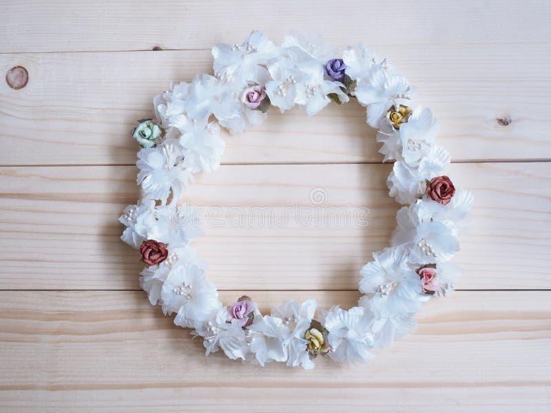 Венок белого цветка с малым поднял на деревянную предпосылку стоковая фотография