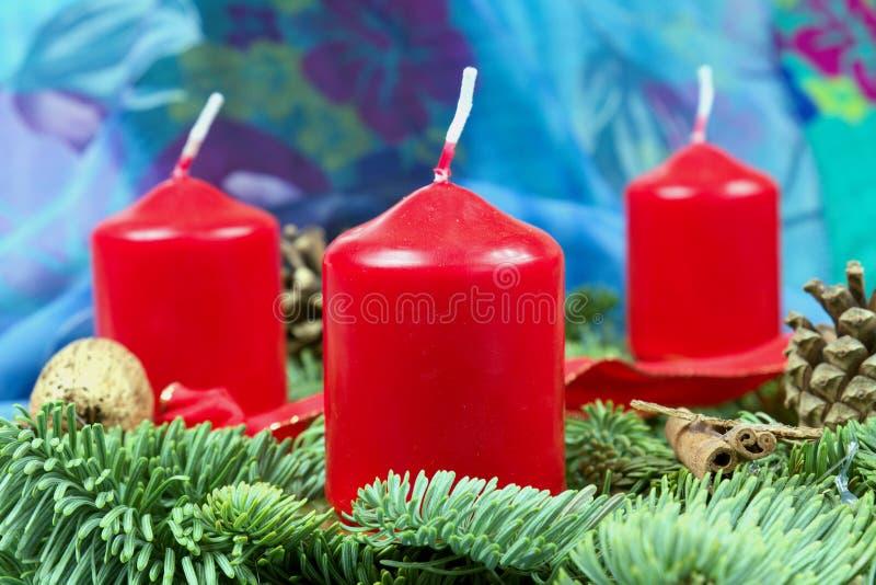 Венок пришествия с красными свечами с голубой предпосылкой стоковое фото