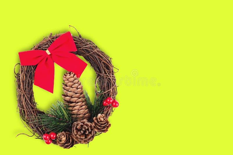 Венок рождества с конусом и хворостиной рождественской елки и красные ветви смычка ткани и сухих на желтой предпосылке стоковое фото rf