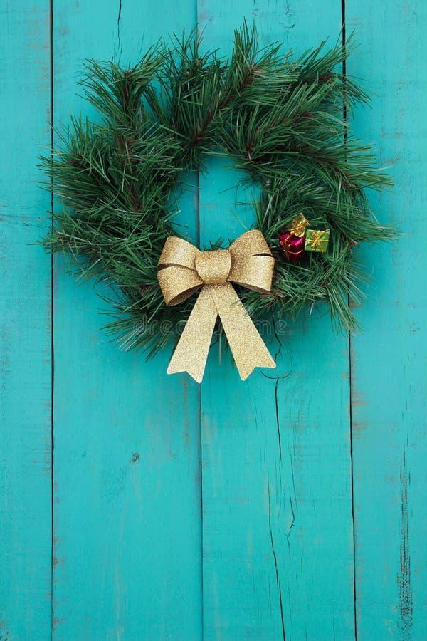 Венок рождества с смертной казнью через повешение смычка золота на предпосылке античного teal голубой деревянной стоковое изображение