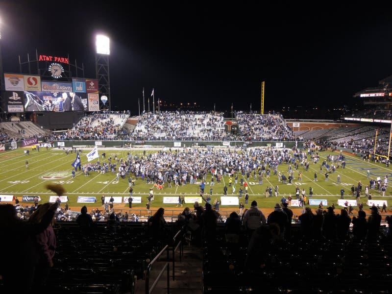 Вентиляторы веселят по мере того как команда-победитель празднует на поле стоковое изображение