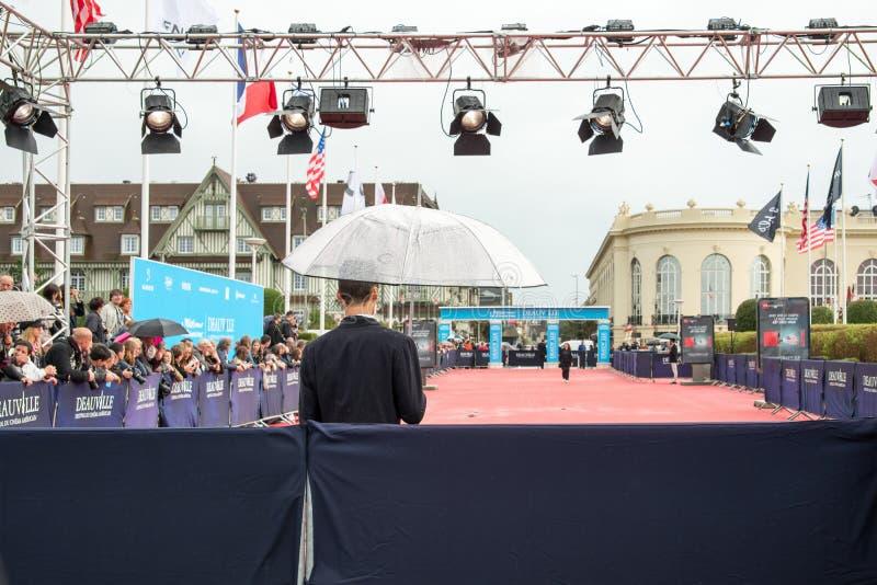 Вентиляторы ждать под дождем для актеров и знаменитостей на красном ковре во время 41st фестиваля фильмов американца Deauville стоковые изображения rf