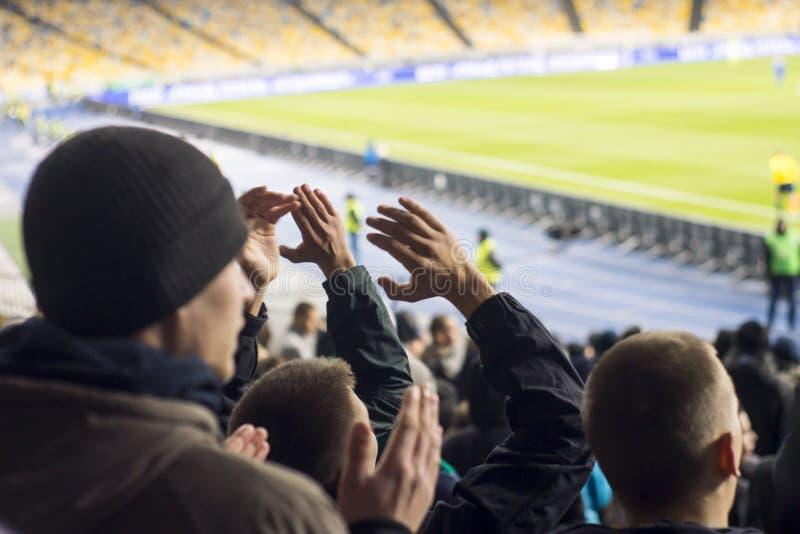 вентиляторы которые хлопают их руки на стадионе стоковая фотография rf