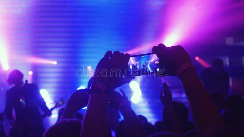 Вентиляторы развевая их записывать рук видео- и фотографировать с умными телефонами на концерте музыки Толпа людей partying на стоковое фото
