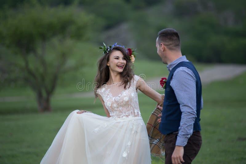 венчание Жених и невеста держа руки и прогулку на зеленом поле стоковые изображения