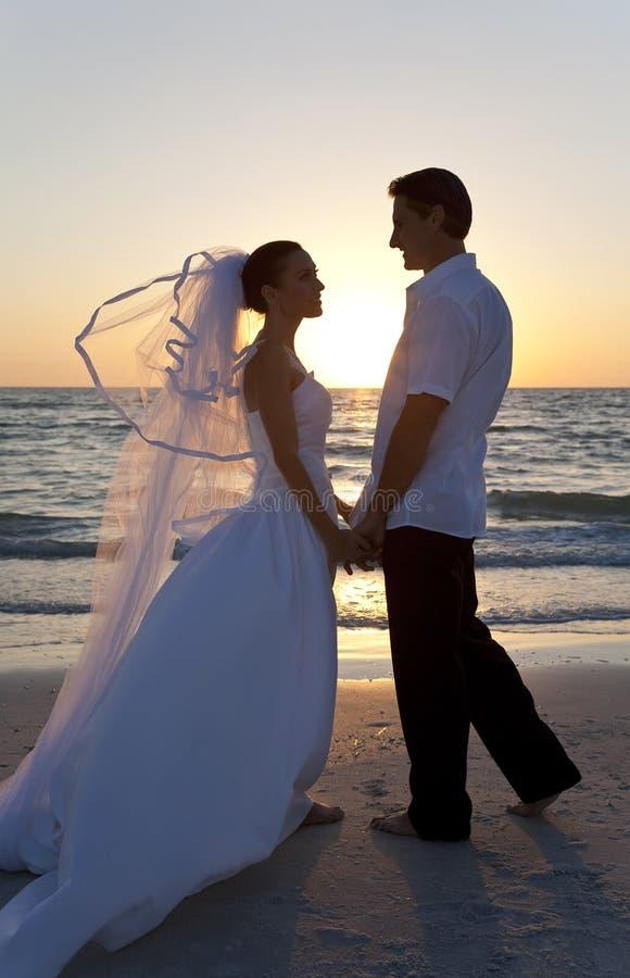 венчание захода солнца пар невесты пляжа пожененное groom стоковые фото