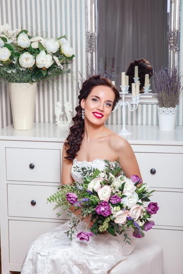 венчание Невеста в красивом платье сидя на софе внутри помещения в белом интерьере студии любит дома Ультрамодный стиль свадьбы стоковое фото rf