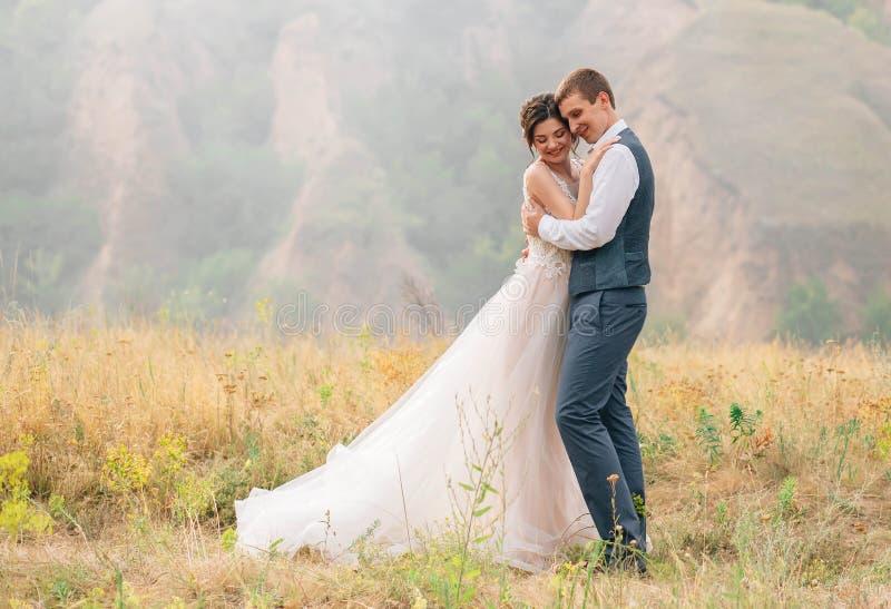 венчание сбора винограда дня пар одежды счастливое Жених и невеста нежно обнимает один другого против фона живой природы на заход стоковое фото rf