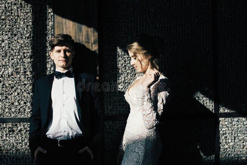 венчание сбора винограда дня пар одежды счастливое Молодая, участливая пара гуляя вокруг города и представляя на фоне розовой сте стоковое фото