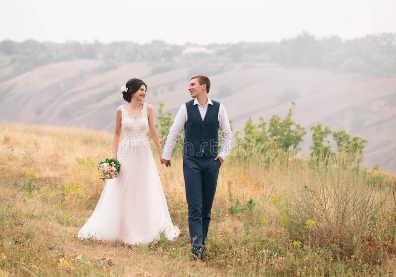венчание сбора винограда дня пар одежды счастливое Стильные молодые пары идя на предпосылку живой природы на заходе солнца Точное стоковые фотографии rf