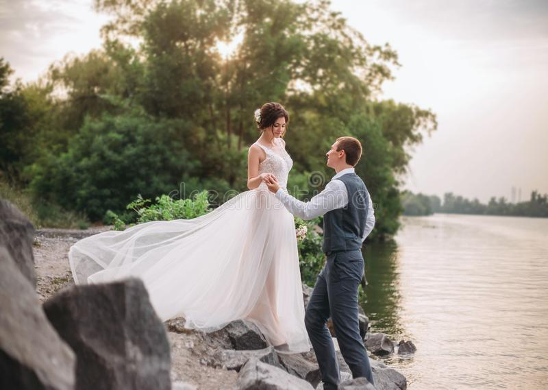 венчание сбора винограда дня пар одежды счастливое Стильные молодые пары идя на предпосылку живой природы на заходе солнца Точное стоковая фотография rf
