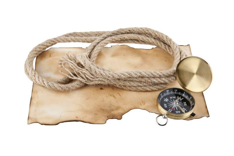 Веревочка и компас на старой бумаге стоковое изображение