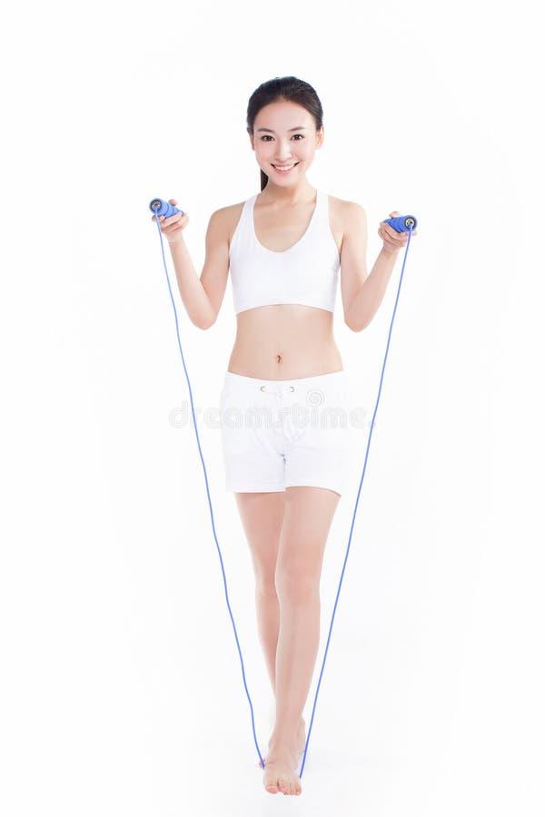 Веревочка маленькой девочки скача, белая предпосылка стоковая фотография rf