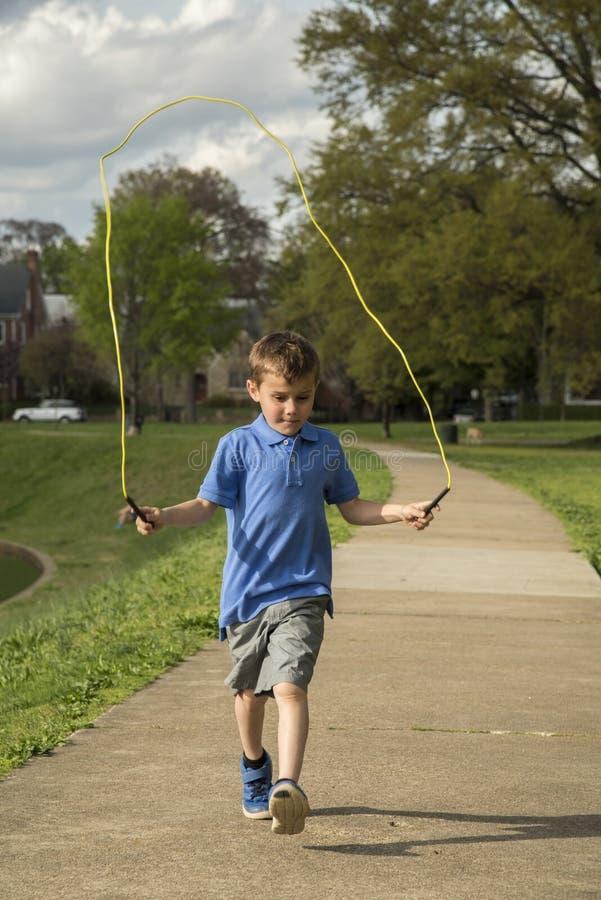 Веревочка мальчика скача в парке стоковая фотография