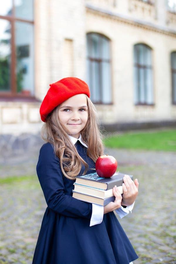 Вернуться в школу Детское образование и школьная концепция Маленькая девочка в красном берете держит стек книг с яблоком Готово к стоковые фото