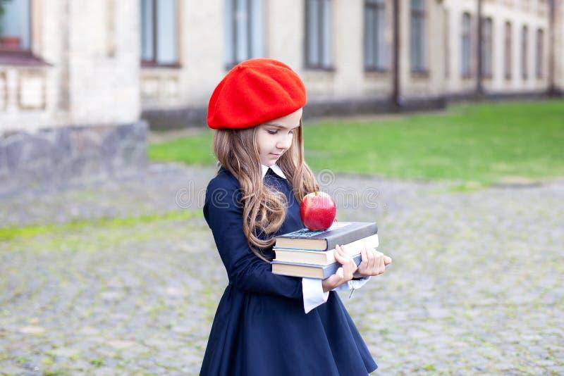 Вернуться в школу Детское образование и школьная концепция Маленькая девочка в красном берете держит стек книг с яблоком Готово к стоковое фото