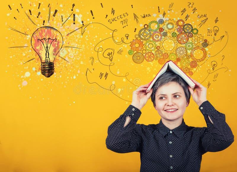 Вернуться к школьной концепции, когда счастливая школьница смотрит в сторону позитивного выражения, держит открытую книгу над гол стоковое изображение