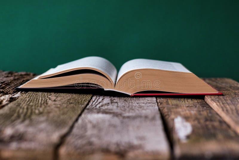 Вернуться к школьной концепции, открыть книгу на старой деревянной пов стоковые изображения
