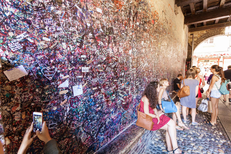 Верона, Италия - 8-ое сентября 2016: Люди сидя и фотографируя около стены которая полна сообщений на различное чужом стоковые фотографии rf