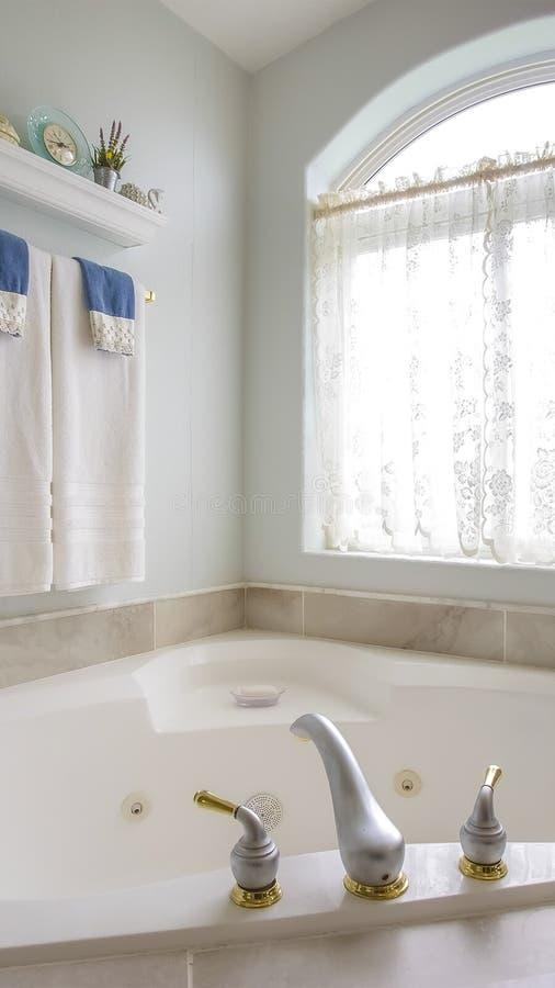 Вертикальная ванна рамки с с золотом и серебряным faucet около сдобренного окна с занавесом стоковая фотография rf